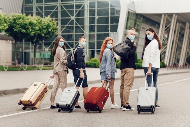 Вид сзади, молодые студенты в защитных масках с чемоданами отправляются учиться за границу после карантина из-за коронавируса