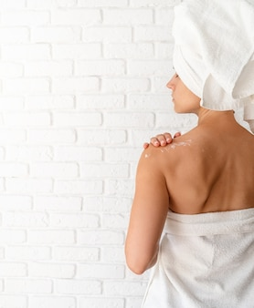 Rear view of a young woman applying cream on her shoulders