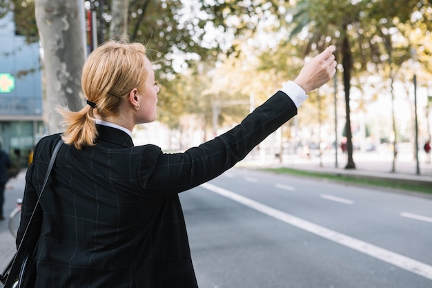 Rear view of a young woman hailing rideshare taxi car on road
