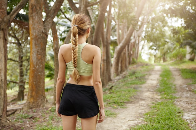 Rear view of young woman jogger with fit body wearing sports bra and black shorts standing alone on trail in tropical forest determined to run.