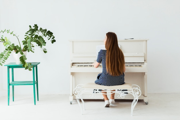Rear view of a young woman playing the piano against white wall