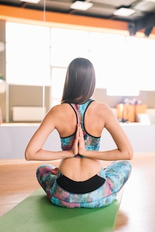 Rear view of young woman practicing yoga
