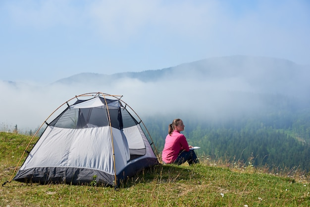 Rear view of young woman sitting on green grass of blooming valley at tourist tent under beautiful blue sky reading a book on bright summer morning on foggy mountains background.