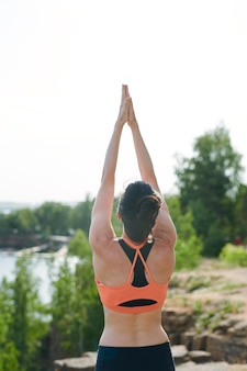 Rear view of young woman in sports bra standing on quarry and raising hands up while doing sun salutation exercise