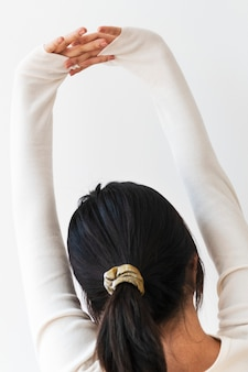 Rear view of a young woman stretching her arms
