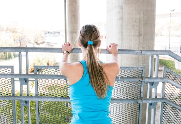 Rear view of a young woman stretching near the railing