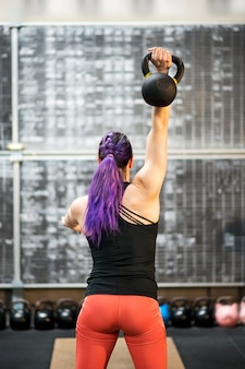 Rear view of a young woman swinging a kettlebell