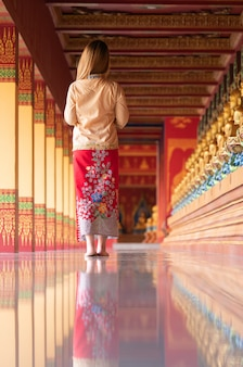 Rear view of young woman in thai's cloth traveling in temple