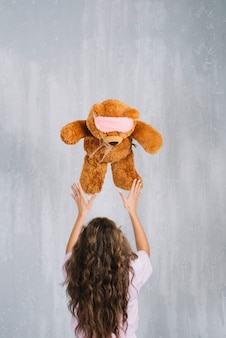 Rear view of a young woman throwing soft toy in mid-air