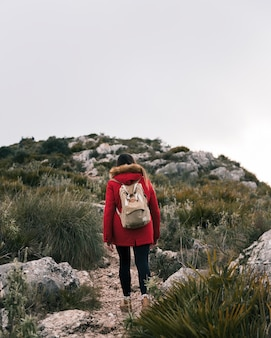 Rear view of young woman walking on mountain trail with her backpack