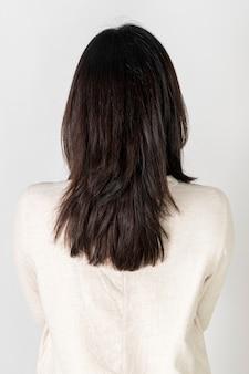 Vista posteriore di una giovane donna che indossa una camicia bianca