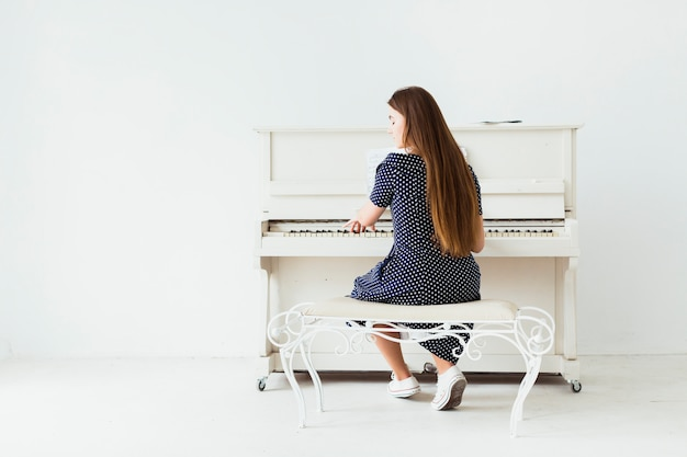 Rear view of a young woman with long hair playing the piano against white wall