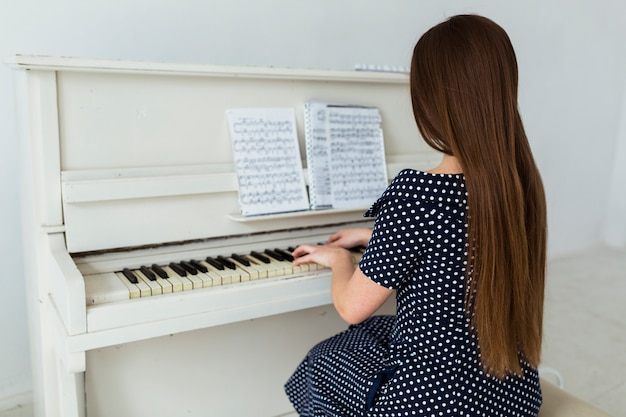 Rear view of young woman with long hair playing piano