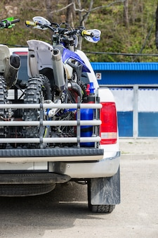 Rear viwe with two dirt bike motorcycles on the back of the truck with safety gear in residential setting.