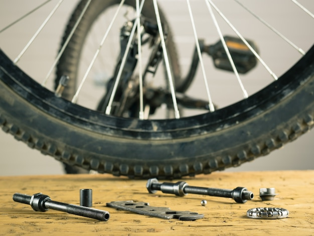 Rear wheel mountain bike and tools on a wooden table.