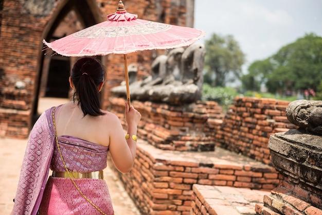 タイのアユタヤにある寺院で、古代の塔と仏像を持ったタイの伝統的な衣装を着た後部の女性。有名な旅行先。