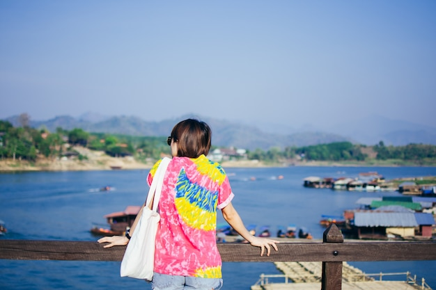 Rear of woman travel and stand on wooden mon bridge at kanchanaburi.