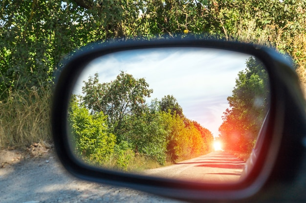 Rearview car driving mirror view green forest and village road