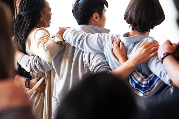 Rearview of diverse people hugging each other