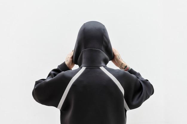 Вид сзади женщины в черной толстовке с капюшоном
