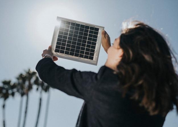 空にソーラーパネルを持ち上げて環境に優しい女性の背面図