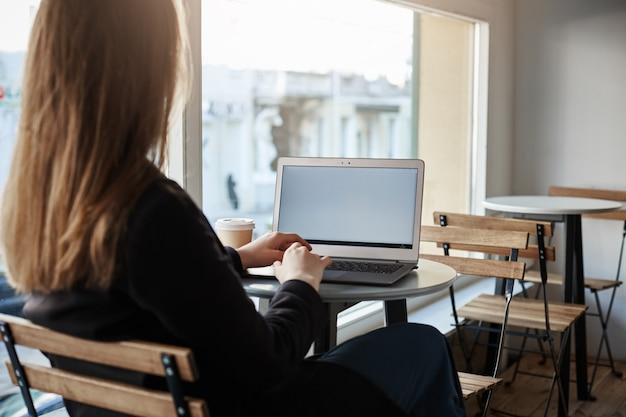 세련된 옷을 입고 성공적인 여성 프리랜서의 백은 노트북에서 작업하는 동안 카페에 앉아