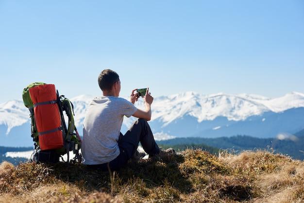 朝のハイキングの後、山の頂上に座っているバックパックを持つ男のバックミラーショット。