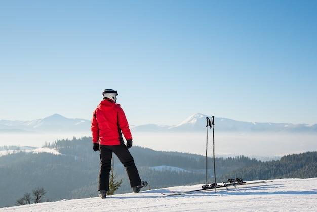 晴れた冬の日に雪に覆われた山々の息をのむような景色を楽しみながら周りを見回すスキー場の斜面に乗って立った後休んでいるスキーヤーのバックミラーショット
