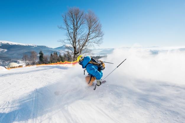 山のスキーリゾートで坂を下ってスキーヤーのバックミラーショット
