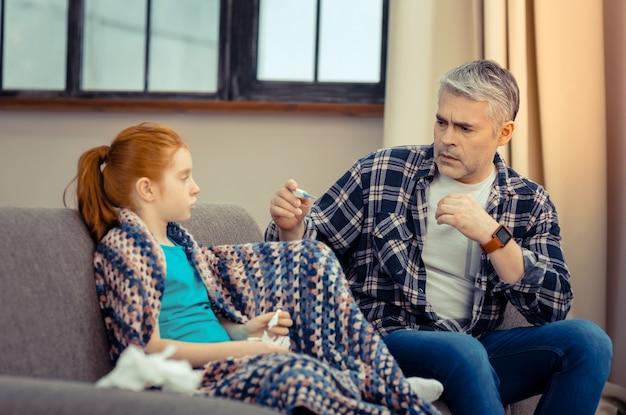 Причина для беспокойства. грустно обеспокоенный отец смотрит на градусник, сидя рядом со своей дочерью