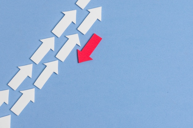Rebel red arrow and crowd of white arrows on blue background
