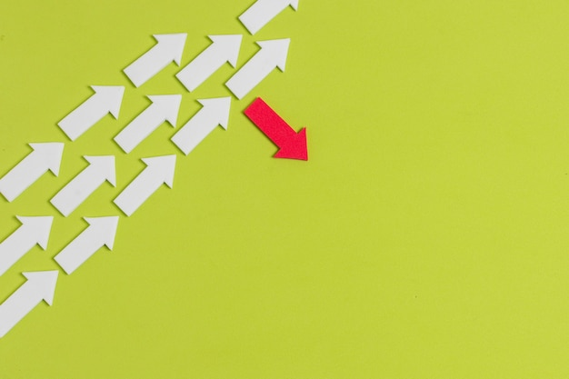 Rebel red arrow and crowd of white arrows on green background