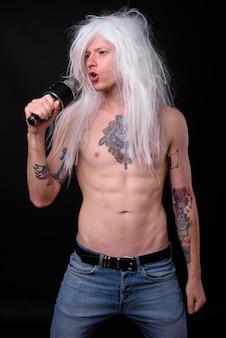Rebellious man as punk rocker wearing wig shirtless against black