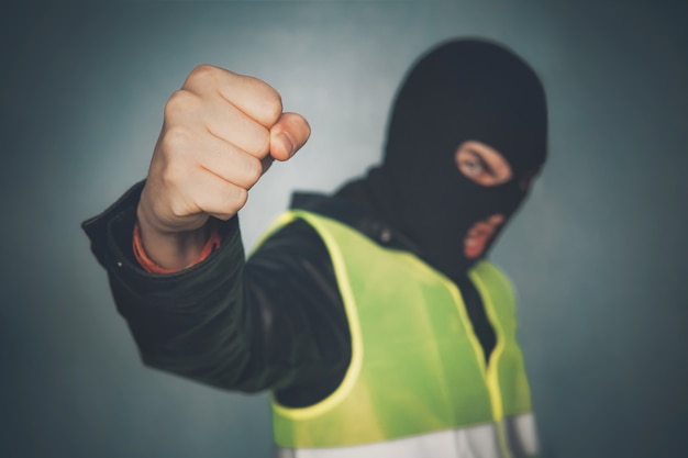 Мятежный протестующий в маске показывает кулак. желтый жилет протеста. уличные беспорядки. французская революция. злой бандит-хулиган угрожает власти. идея борьбы бедных пролетариев против правительства и системы.