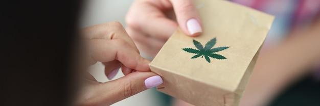 紙袋に緑のマリファナの葉が付いた薬のクラフトバッグを受け取ります。