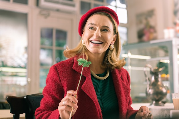 Receiving flower. happy beaming mature woman wearing red beret feeling amazing after receiving flower
