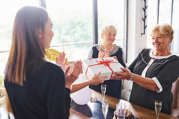 Receiving gift box. senior woman with family and friends celebrating a birthday indoors.