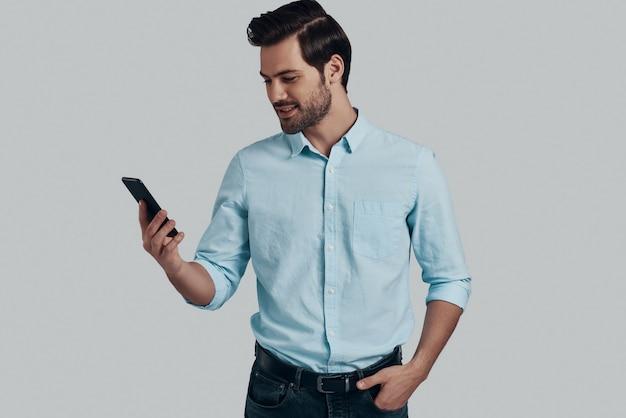 友達からのメッセージを受信します。スマートフォンを使用して、灰色の背景に立って笑っているハンサムな若い男