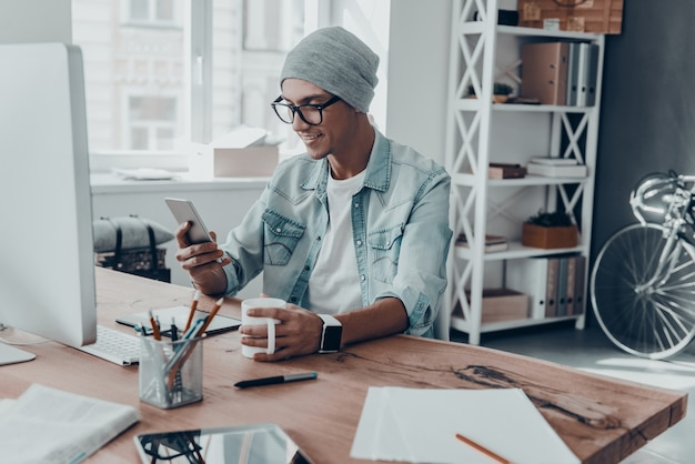 Получение приятных сообщений. красивый молодой человек держит чашку и смотрит на смартфон с улыбкой
