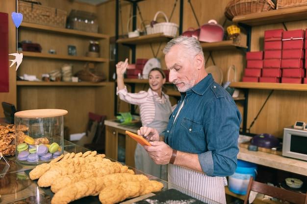 주문을 받고 있습니다. 그들의 프랑스 빵집에서 주문을 받고 번영하는 성공적인 사업가 부부