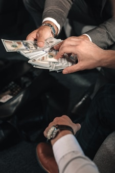 Receiving payoff. man wearing hand watch and white shirt receiving payoff from business partner