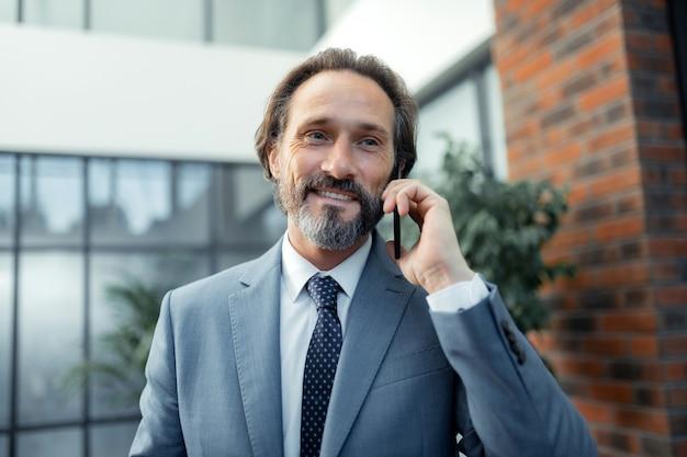 電話を受ける。彼の妻からの電話を受けながら笑顔でスタイリッシュなネクタイを身に着けているビジネスマン