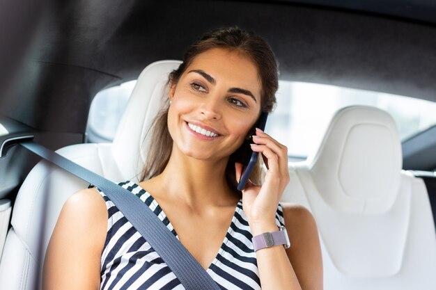 Прием телефонного звонка. темноглазая красивая молодая женщина улыбается, принимая телефонный звонок от друга
