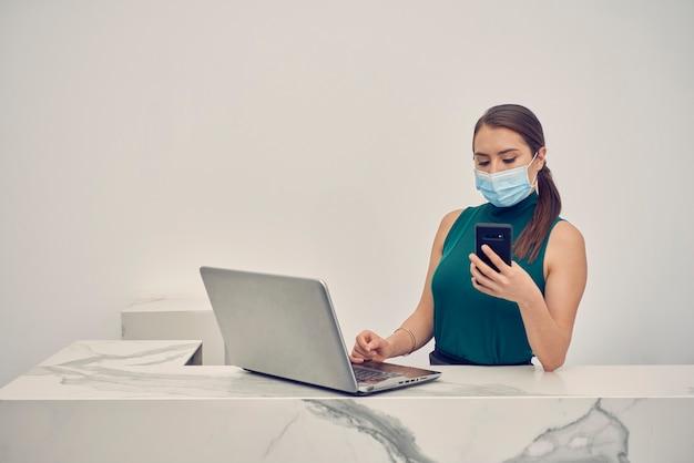 Recepcionista concubrebocasコンテストとmensajesen su celular mientras trabaja