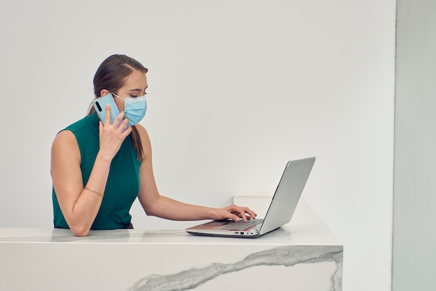 Recepcionista latina con cubrebocas hablando por telefono mientras trabaja en su портативный компьютер