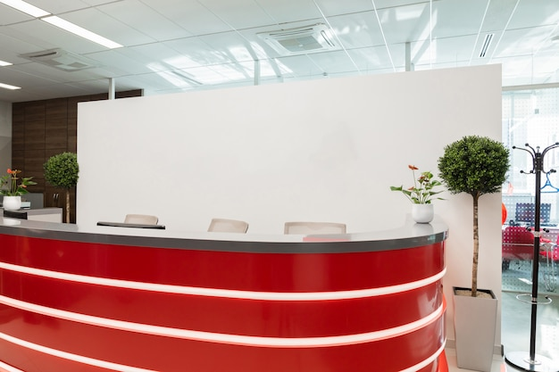Reception area for visitors of modern office with red-white interior