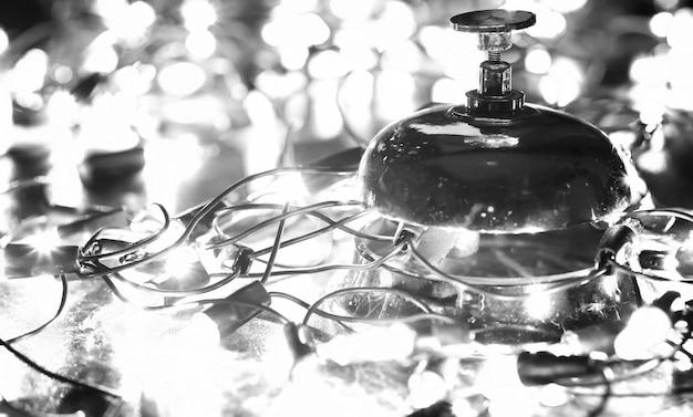 Колокольчик на столе и цветная сияющая гирлянда на фоне