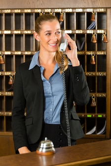 Reception of hotel, desk clerk taking a call