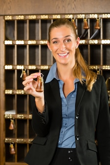Reception of hotel, woman holding key in hand