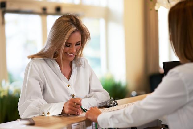 Портье и бизнесвумен на стойке регистрации отеля